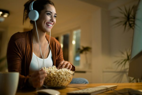 Young happy woman with headphones watching movie on a computer and eating popcorn in the evening at home.